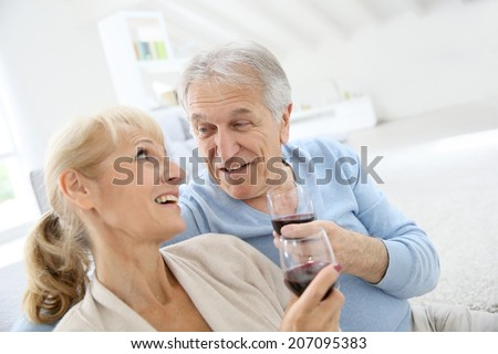 Senior couple at home drinking red wine - stock photo