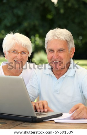Senior couple at home surfing on internet - stock photo