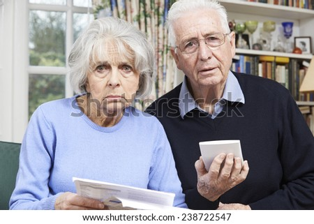 Senior Couple At Home With Bills Worried About Home Finances - stock photo