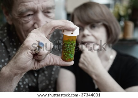 Senior couple at home with prescription bottle, focus - stock photo