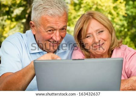 Senior couple browsing on laptop outdoors. Positive expression - stock photo