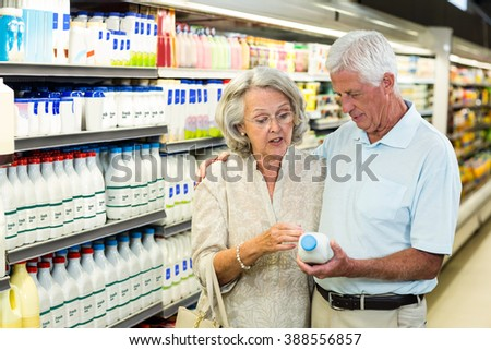 Senior couple buying milk at the supermarket - stock photo