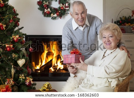 Senior couple celebrating Christmas together in front of fireplace  - stock photo