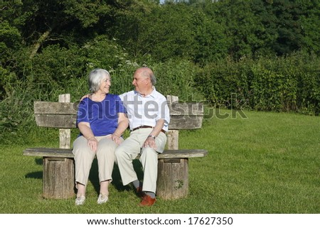Senior couple chatting on a park bench on a summers evening. - stock photo