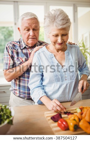 Senior couple chopping vegetables in kitchen - stock photo