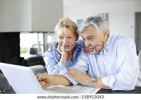 Senior couple connected with family on internet - stock photo