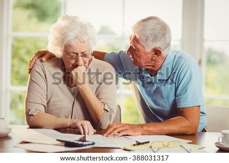 Senior couple counting bills at home - stock photo