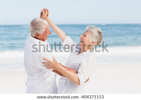 Senior couple dancing on the beach on a sunny day - stock photo