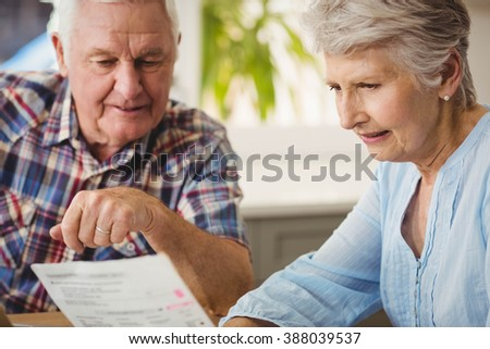 Senior couple discussing their bills at home - stock photo