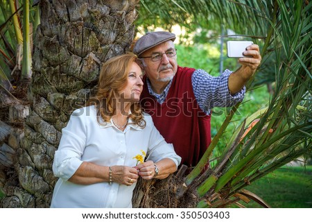 Senior couple doing a self-portrait. They are 75 years old - stock photo