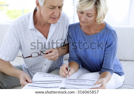 Senior couple doing home finances - stock photo