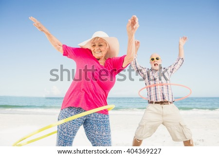 Senior couple doing hula hoop on the beach - stock photo