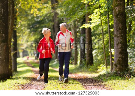Senior Couple doing sport outdoors, jogging on a forest road in the autumn - stock photo