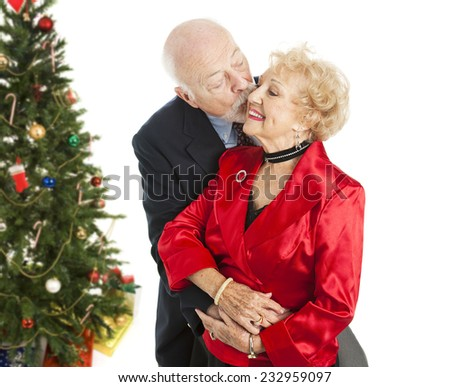 Senior couple dressed for the holidays.  He's giving her a kiss on the cheek.  Isolated with Christmas tree in background.   - stock photo