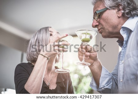Senior couple drinking cocktail at home. Celebrating their anniversary with a toast before dinner - stock photo