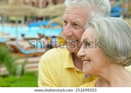 Senior couple drinking juice in pool at hotel resort - stock photo