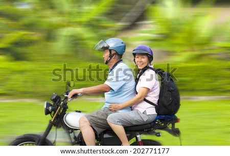 senior couple driving motorcycle with dynamic background - stock photo
