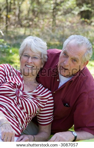 Senior couple during a picnic in the field enjoying each others company - stock photo