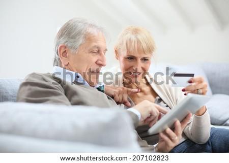 Senior couple e-shopping with digital tablet - stock photo