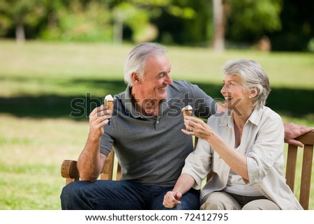 Senior couple eating an ice cream on a bench - stock photo