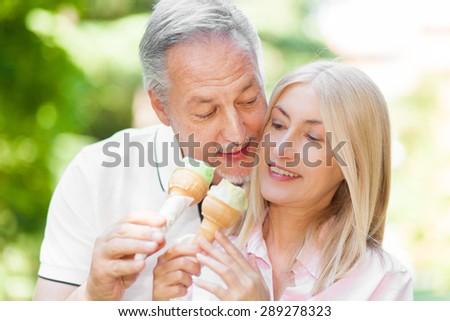 Senior couple eating an ice cream outdoor - stock photo