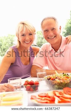 Senior couple eating outdoors - stock photo