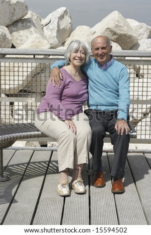 Senior couple embrace on a seaside bench. - stock photo