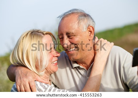 Senior couple embracing each other in countryside and and make selfi with phone - stock photo