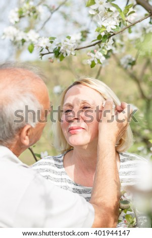 Senior couple enjoying a moment in their blossoming garden, he puts a flower in her hair. - stock photo