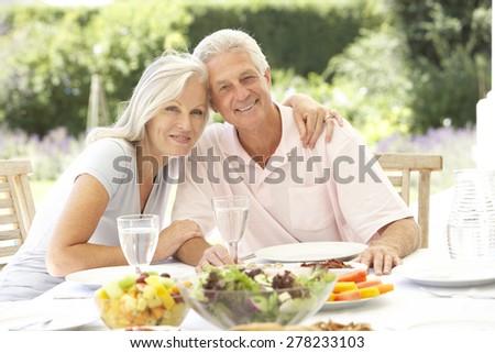 Senior couple enjoying al fresco meal - stock photo