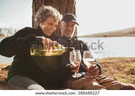 Senior couple enjoying drinks at campsite near Lake. Mature woman pouring wine in glasses, both sitting under a tree on a summer day. - stock photo