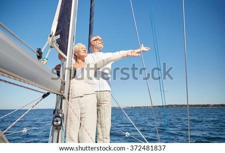 senior couple enjoying freedom on sail boat in sea - stock photo