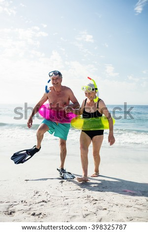 Senior couple enjoying on beach on a sunny day - stock photo
