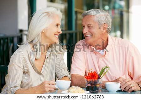 Senior Couple Enjoying Snack At Outdoor Cafe - stock photo