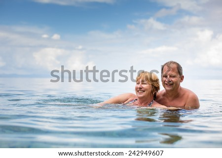 Senior couple enjoying the retirement on a seacost, having a swim in the sea, laughing togther, staying active and positive - stock photo
