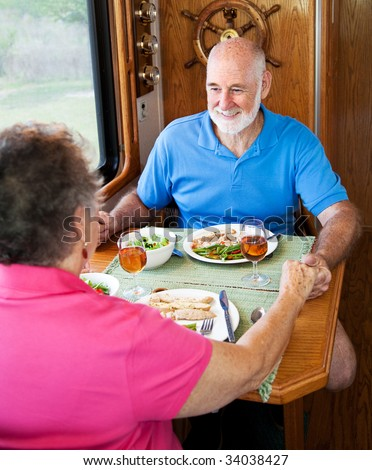 Senior couple enjoys conversation over a healthy meal in their motor home. - stock photo