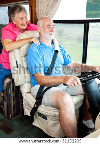 Senior couple enjoys riding in their motor home. - stock photo