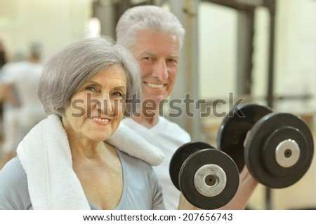 Senior couple exercising in a gym with dumbbell - stock photo