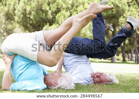Senior Couple Exercising In Garden Together - stock photo