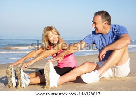 Senior Couple Exercising On Beach - stock photo