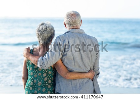 Senior couple facing the sea at the beach - stock photo