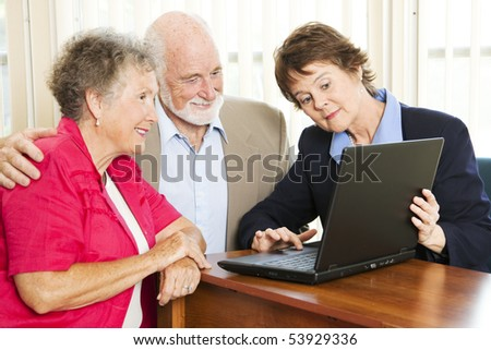 Senior couple getting financial advice or a sales pitch. - stock photo