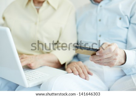 Senior couple hands with credit card and laptop during shopping through Internet - stock photo