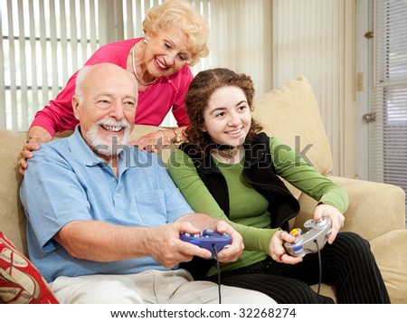 Senior couple has fun playing video games with their teenage granddaughter. - stock photo
