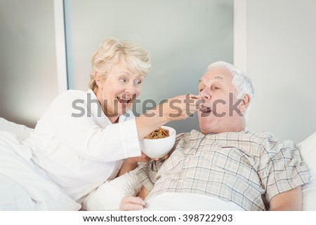 Senior couple having breakfast in bed at home - stock photo