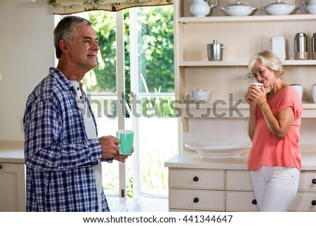 Senior couple having coffee in kitchen at home - stock photo