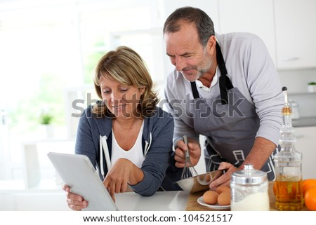 Senior couple having fun in home kitchen - stock photo
