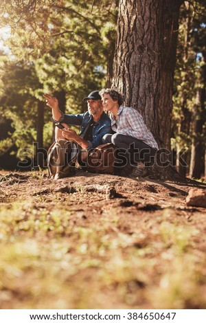 Senior couple hiking in nature with man holding a compass and showing the direction to woman. Couple during hike using a compass in the countryside - stock photo