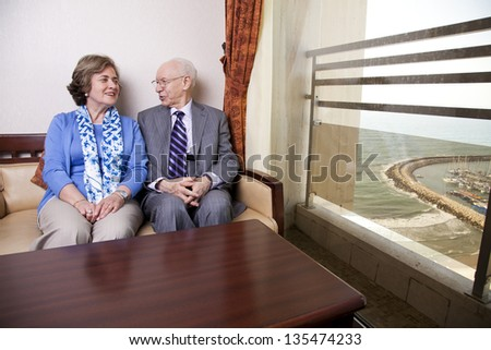 Senior couple (his 80's, her late 60's) sitting on a sofa, looking very much in love. The man is looking at the woman as she is glancing at the window, where the seashore and a marina can be seen. - stock photo