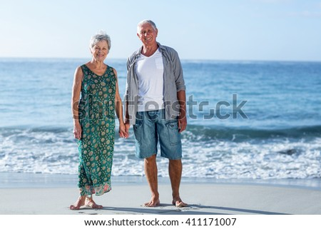 Senior couple holding hands on the beach - stock photo
